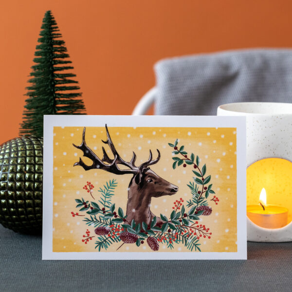 Photo of a greeting card featuring a stag with antlers on a mustard yellow background, surrounded by a wreath of wintery red and green foliage and snowflakes