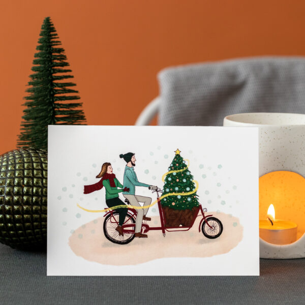 Photo of a greeting card featuring a couple on a cargo bike cycling their christmas tree home in the snow