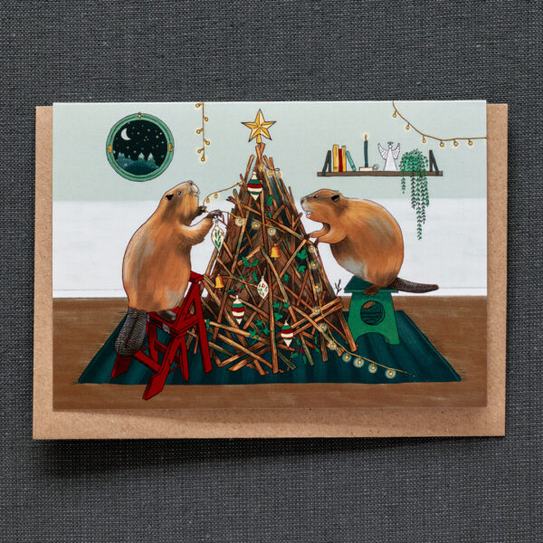 Photo of a greeting card featuring two beavers in their living room, decorating a christmas tree made up from sticks like a beaver's dam.