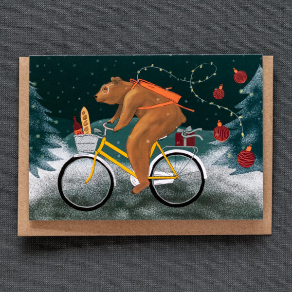 Photo of a greeting card featuring a brown bear wearing glasses, cycling through the snow to a holiday party. The yellow bicycle has a front basket containing bread and wine, and there are decorations trailing from the bear's red backpack.